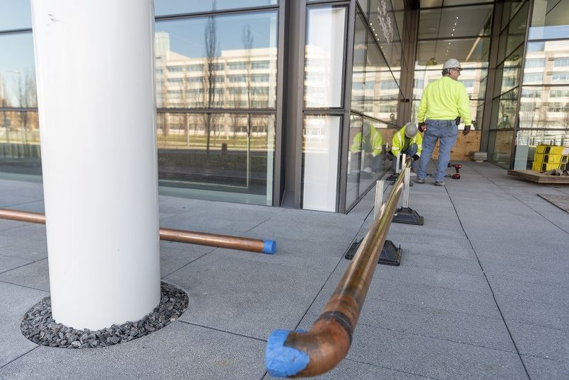 Pipefitters working on a new copper pipe outside an office building